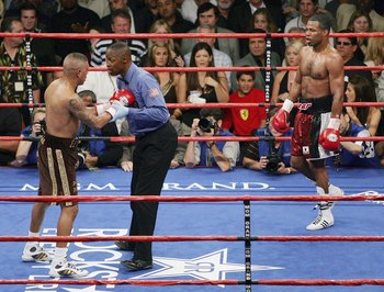 LAS VEGAS - JULY 15:  Referee Kenny Bayless (C) checks on Fernando Vargas (L) after he was knocked to the canvas by Shane Mosley (R) in the sixth round of their junior middleweight rematch at the MGM Grand Garden Arena July 15, 2006 in Las Vegas, Nevada.