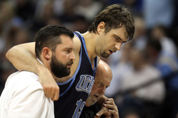 DENVER, CO - APRIL 17 : Mehmet Okur #13 of the Utah Jazz is helped off the court by trainers after twisitng an ankle during the first half of Game One of the Western Conference Quarterfinals of the 2010 NBA Playoffs at the Pepsi Center on April 17, 2010 i