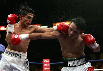 LAS VEGAS - JANUARY 21:  (L-R)  Erik Morales of Mexico throws a left at Manny Pacquiao of the Phillippines during their Super Featherweight Championship fight at Thomas & Mack Arena on January 21, 2006 in Las Vegas, Nevada.  (Photo by Jed Jacobsohn/Getty