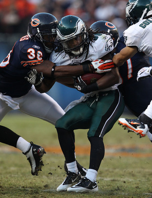 CHICAGO - NOVEMBER 28: Jorrick Calvin #38 of the Philadelphia Eagles is tackled by D.J. Moore #30 and Kellen Davis #87 of the Chicago Bears at Soldier Field on November 28, 2010 in Chicago, Illinois. The Bears defeated the Eagles 31-26. (Photo by Jonathan