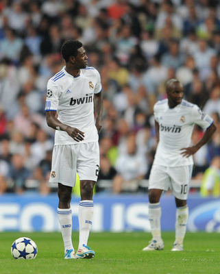 MADRID, SPAIN - APRIL 27:  Emmanuel Adebayor (L) of Real Madrid trudges back to the halfway line backdropped by his teammate Lassana Diarra after conceding a goal during the UEFA Champions League Semi Final first leg match between Real Madrid and Barcelon