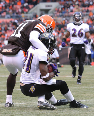 CLEVELAND - DECEMBER 26:  Cornerback Lardarius Webb #21 of the Baltimore Ravens intercepts the ball as he is hit by wide receiver Mohamed Massaquoi #11 of the Cleveland Browns look on at Cleveland Browns Stadium on December 26, 2010 in Cleveland, Ohio.  (