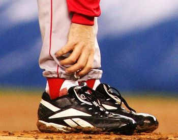 NEW YORK - OCTOBER 19:   Pitcher Curt Schilling #38 of the Boston Red Sox grabs at his ankle as it appears to be bleeding in the fourth inning during game six of the American League Championship Series against the New York Yankees on October 19, 2004 at Y