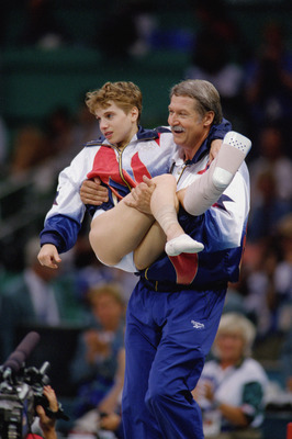 ATLANTA - JULY 23:  Coach Bela Karolyi carries Kerri Strug of the United States after she injured herself on her first attempt while competing in the vault, part of the Womens Team Gymnastics competition at the 1996 Olympic Games on July 23, 1996 at the G