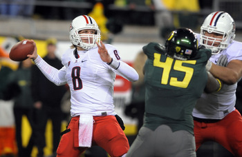 EUGENE, OR - NOVEMBER 26: Quarterback Nick Foles #8 of the Arizona Wildcats passes the ball as defensive end Terrell Turner #45 of the Oregon Ducks applies pressure in the fourth quarter of the game at Autzen Stadium on November 26, 2010 in Eugene, Oregon