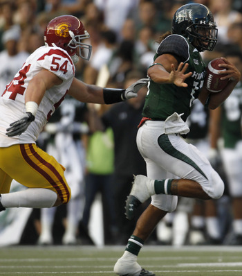 HONOLULU - SEPTEMBER 02: Quarterback Bryant Moniz #17 of the University of Hawaii Warriors is chased by Chris Galippo #54 of the University of Southern California Trojans as he carries the ball during first half action against the University of Southern C