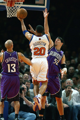 NEW YORK - JANUARY 4:  Allan Houston #20 of the New York Knicks drives to the basket against Brad Miller #52 of the Sacramento Kings on January 4, 2005 at Madison Square Garden in New York City. The Kings won 105-98.  NOTE TO USER: User expressly acknowle