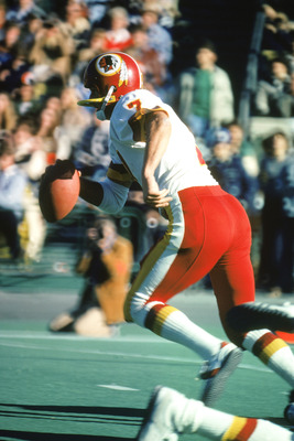 CHICAGO -1980:  Joe Theismann #7 of the Washington Redskins runs as he looks to pass during the 1980 NFL season game against the Chicago Bears at Soldier Field in Chicago, Illinois. The Bears defeated the Redskins 35-21. (Photo by: Jonathan Daniel/Getty I