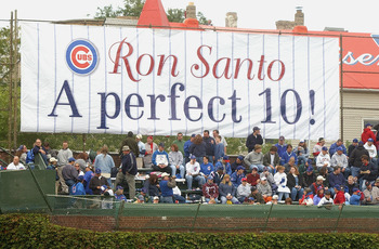CHICAGO - SEPTEMBER 28:  Fans of the Chicago Cubs watch the game in front of a sign honoring longtime Cubs third baseman and current WGN Radio color commentator Ron Santo (Santo's number 10 was retired in a pregame ceremony) during a game against the Pitt