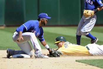 OAKLAND, CA - MAY 1: Elvis Andrus #1 of the Texas Rangers tags out Cliff Pennington #2 of the Oakland Athletics attempting to steal second base during a MLB baseball game at the Oakland-Alameda County Coliseum May 1, 2011 in Oakland, California. (Photo by
