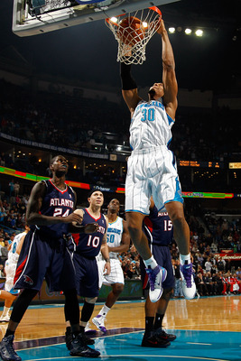 NEW ORLEANS, LA - DECEMBER 26:  David West #30 of the New Orleans Hornets dunks the ball over Marvin Williams #24 of the Atlanta Hawks at the New Orleans Arena on December 26, 2010 in New Orleans, Louisiana.  NOTE TO USER: User expressly acknowledges and