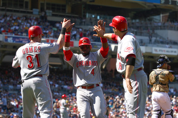 SAN DIEGO, CA - SEPTEMBER 26:  Jonny Gomez #31 and Joey Votto #19 congratulate Brandon Phillips #4 of Cincinnati Reds after their teammate Chris Heisey #28 hit a 3-RBI double against the San Diego Padres during the 4th inning of their MLB game on Septembe