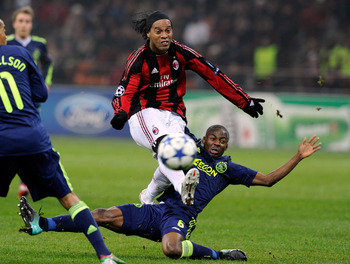 MILAN, ITALY - DECEMBER 08:  Ronaldinho of AC Milan and Eyong Enoh of AFC Ajax compete for the ball during the UEFA Champions League Group G match between AC Milan and AFC Ajax at Stadio Giuseppe Meazza on December 8, 2010 in Milan, Italy.  (Photo by Clau