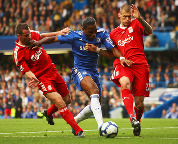 LONDON - OCTOBER 04:  Martin Skrtel (R) and Jamie Carragher of Liverpool (L) tussle with Didier Drogba of Chelsea during the Barclays Premier League match between Chelsea and Liverpool at Stamford Bridge on October 4, 2009 in London, England.  (Photo by I