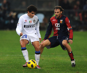 GENOA, ITALY - OCTOBER 29: Coutinho of FC Internazionale Milano shields the ball from Marco Rossi of Genoa CFCduring the Serie A match between Genoa CFC  and FC Inter Milan at Stadio Luigi Ferraris on October 29, 2010 in Genoa, Italy.  (Photo by Massimo C