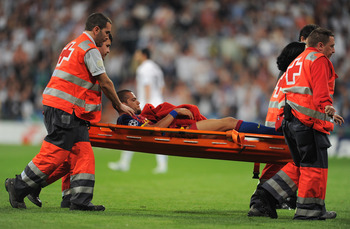 MADRID, SPAIN - APRIL 27:  Daniel Alves of Barcelona is stretchered off the pitch after being fouled by Pepe of Real Madrid during the UEFA Champions League Semi Final first leg match between Real Madrid and Barcelona at the Estadio Santiago Bernabeu on A