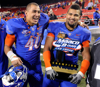 LAS VEGAS, NV - DECEMBER 22:  Tyrone Crawford #40 and Billy Winn #90 of the Boise State Broncos celebrate with a trophy after the team's 26-3 victory over the Utah Utes in the MAACO Bowl Las Vegas at Sam Boyd Stadium December 22, 2010 in Las Vegas, Nevada