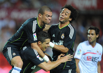 SEVILLE, SPAIN - MAY 07: Cristiano Ronaldo (C) of Real Madrid celebrates with Pepe (L) and Marcelo   after Ronaldo scored Real's second goal during the La Liga match between Sevilla and Real Madrid at Estadio Ramon Sanchez Pizjuan on May 7, 2011 in Sevill