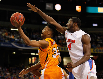 ATLANTA, GA - MARCH 11:  Scotty Hopson #32 of the Tennessee Volunteers goes up for a shot in front of Patric Young #4 of the Florida Gators during the quarterfinals of the SEC Men's Basketball Tournament at Georgia Dome on March 11, 2011 in Atlanta, Georg