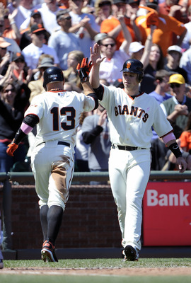 SAN FRANCISCO, CA - MAY 8: Cody Ross #13 of the San Francisco Giants high-fives Buster Posey #28  after hitting a two-run homer in the bottom of the six inning against the Colorado Rockies during a MLB baseball game at AT&T Park May 8, 2011 in San Francis