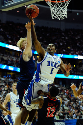 ANAHEIM, CA - MARCH 24:  Kyrie Irving #1 of the Duke Blue Devils draws contact against Kyryl Natyazhko #1 and Lamont Jones #12 of the Arizona Wildcats during the west regional semifinal of the 2011 NCAA men's basketball tournament at the Honda Center on M