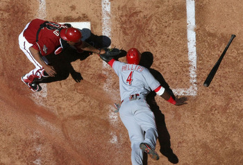 PHOENIX, AZ - APRIL 10:  Brandon Phillips #4 of the Cincinnati Reds is tagged out at home plate by catcher Henry Blanco #12 of the Arizona Diamondbacks as he attempts to score during the second inning of the Major League Baseball game at Chase Field on Ap