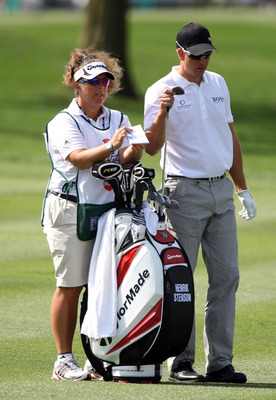 ORLANDO, FL - MARCH 25:  Henrik Stenson of Sweden pulls a club in the first fairway as his caddie Fanny Sunnesson looks on during the first round of the Arnold Palmer Invitational presented by MasterCard at the Bayhill Club and Lodge on March 25, 2010 in