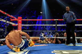 LAS VEGAS, NV - MAY 07:  Manny Pacquiao of the Philippines is knocked down in the 10th round by Shane Mosley as referee Kenny Bayless watches in the WBO welterweight title fight at MGM Grand Garden Arena on May 7, 2011 in Las Vegas, Nevada.  (Photo by Chr