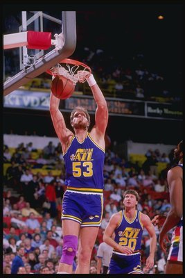1989-1990:  Center Mark Eaton of the Utah Jazz slam dunks as teammate guard Bobby Hansen (right) looks on during a game against the Denver Nuggets at McNichols Arena in Denver, Colorado. Mandatory Credit: Tim de Frisco  /Allsport