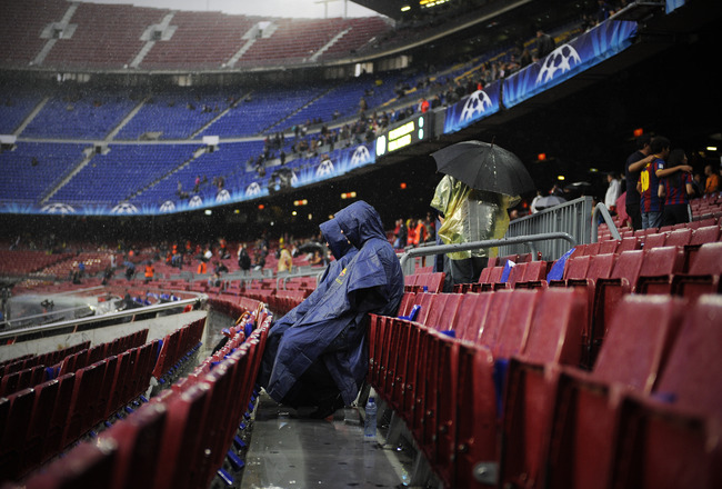 BARCELONA, SPAIN - MAY 03:  Two spectators sit on the  stands under heavy rain prior to the UEFA Champions League Semi Final second leg match between Barcelona and Real Madrid at the Nou Camp on May 3, 2011 in Barcelona, Spain.  (Photo by David Ramos/Gett