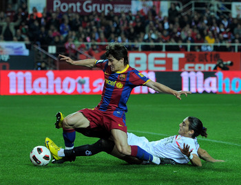 SEVILLE, SPAIN - MARCH 13:  Bojan Krkic (L) of Barcelona scores his sides opening goal past Jose Caceres of Sevilla during the la Liga match between Sevilla and Barcelona at Estadio Ramon Sanchez Pizjuan on March 13, 2011 in Seville, Spain.  (Photo by Jas