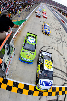 DOVER, DE - SEPTEMBER 26:  Jimmie Johnson, driver of the #48 Lowe's Chevrolet, and A.J. Allmendinger, driver of the #43 Insignia HDTV Ford, lead the field to the green flag to start the NASCAR Sprint Cup Series AAA 400 at Dover International Speedway on S
