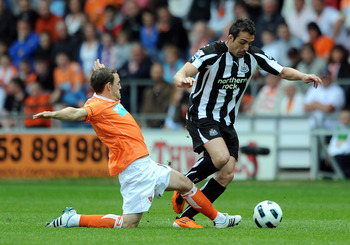 BLACKPOOL, ENGLAND - APRIL 23:  David Vaughan of Blackpool challenges Jose Enrique of Newcastle United during the Barclays Premier League match between Blackpool and Newcastle United at Bloomfield Road on April 23, 2011 in Blackpool, England.  (Photo by C