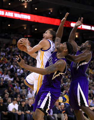 OAKLAND, CA - JANUARY 21:  Stephen Curry #30 of the Golden State Warriors drives on DeMarcus Cousins #15 and Tyreke Evans #13 of the Sacramento Kings at Oracle Arena on January 21, 2011 in Oakland, California. NOTE TO USER: User expressly acknowledges and