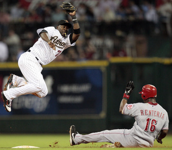 HOUSTON - MAY 09:  Second baseman Bill Hall #22 of the Houston Astros leaps to catch a throw from catcher J.R. Towles as Edgar Renteria #16 of the Cincinnati Reds slides in safely at Minute Maid Park on May 9, 2011 in Houston, Texas.  (Photo by Bob Levey/