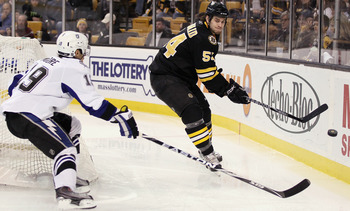 BOSTON, MA - MARCH 03:  Adam McQuaid #54 of the Boston Bruins clears the puck as Dominic Moore #19 of the Tampa Bay Lightning tries to make the steal on March 3, 2011 at the TD Garden in Boston, Massachusetts.  (Photo by Elsa/Getty Images)