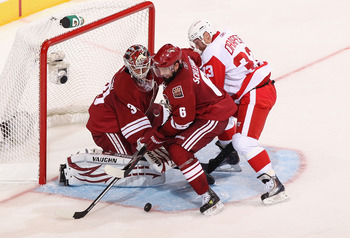 GLENDALE, AZ - APRIL 20:  David Schlemko #6 of the Phoenix Coyotes attempts to clear the puck from goaltender Ilya Bryzgalov #30 as Kris Draper #33 of the Detroit Red Wings skates in Game Four of the Western Conference Quarterfinals during the 2011 NHL St