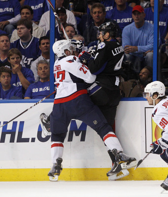 TAMPA, FL - MAY 03: Karl Alzner #27 of the Washington Capitals hits Vincent Lecavalier #4 of the Tampa Bay Lightning into the boards in Game Three of the Eastern Conference Semifinals during the 2011 NHL Stanley Cup Playoffs at St Pete Times Forum on May