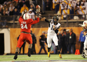ORLANDO, FL - DECEMBER 28:  Geno Smith #12 of the West Virginia Mountineers passes over George Bryan #84 of the North Carolina State Wolfpack during the Champs Sports Bowl at Florida Citrus Bowl Stadium on December 28, 2010 in Orlando, Florida.  (Photo by