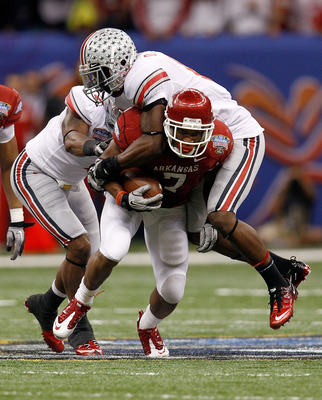 NEW ORLEANS, LA - JANUARY 04:  Knile Davis #7 of the Arkansas Razorbacks runs the ball as Orhian Johnson #19 of the Ohio State Buckeyes attempts to tackle him in the second quarter during the Allstate Sugar Bowl at the Louisiana Superdome on January 4, 20
