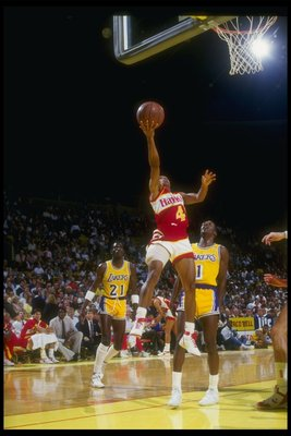 Point guard Anthony (Spud) Webb of the Atlanta Hawks goes to the hoop while the defenders of the Los Angeles Lakers look on during a game at The Forum in Inglewood, California