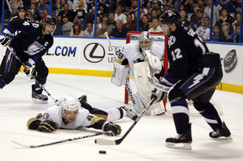 TAMPA, FL - APRIL 20: Goaltender Marc-Andre Fleury #29 of the Pittsburgh Penguins defends the net with the help of teammate Zbynek Michalek #4 against Simon Gagne #12 of the Tampa Bay Lightning in the first overtime period in Game Four of the Eastern Conf