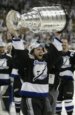 TAMPA, FL - JUNE 7:  Martin St. Louis #26 of the Tampa Bay Lightning holds the Stanley Cup above his head after the victory over the Calgary Flames in Game seven of the NHL Stanley Cup Finals on June 7, 2004 at the St. Pete Times Forum in Tampa, Florida.