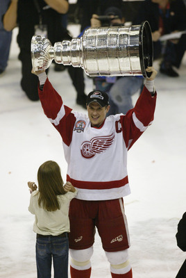 DETROIT, MI - JUNE 13:  Steve Yzerman #19 of the Detroit Red Wings and his daughter Isabella celebrate with the Stanley Cup trophy after defeating the Carolina Hurricanes during game 5 of the 2002 Stanley Cup Finals on June 13, 2002 at Joe Louis Arena in