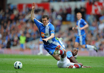 BIRMINGHAM, ENGLAND - MAY 07: Darren Bent of Villa tackles Gary Caldwell of Wigan during the Barclays Premier League match between Aston Villa and Wigan Athletic on May 7, 2011 in Birmingham, England.  (Photo by Michael Regan/Getty Images)