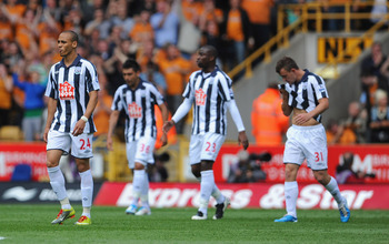 WOLVERHAMPTON, ENGLAND - MAY 08: Peter Odemwingie looks dejected with team mates after the 2nd Wolves goal during the Barclays Premier League match between Wolverhampton Wanderers and West Bromwich Albion at Molineux on May 8, 2011 in Wolverhampton, Engla