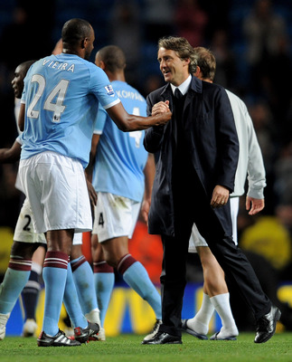 MANCHESTER, ENGLAND - MAY 10:  Manchester City Manager Roberto Mancini congratulates Patrick Vieira  at the end of the Barclays Premier League match between Manchester City and Tottenham Hotspur at the City of Manchester Stadium on May 10, 2011 in Manches