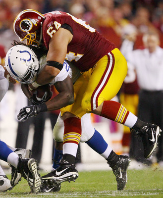 LANDOVER, MD - OCTOBER 17:  Running back Joseph Addai #29 of the Indianapolis Colts is tackled by Kedric Golston #64 of the Washington Redskins at FedEx Field on October 17, 2010 in Landover, Maryland. The Colts won the game 27-24.  (Photo by Win McNamee/