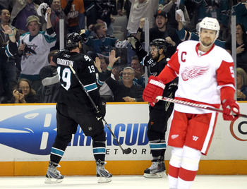 SAN JOSE, CA - MAY 08:  Joe Thornton #19 and Devin Setoguchi #16 of the San Jose Sharks celebrate behind Nicklas Lidstrom #5 of the Detroit Red Wings after Setoguchi scored a goal in Game Five of the Western Conference Semifinals during the 2011 NHL Stanl