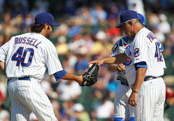 CHICAGO - JULY 21: Manager Lou Piniella #41 of the Chicago Cubs gives the ball to James Russell #40 during a game against the Houston Astros at Wrigley Field on July 21, 2010 in Chicago, Illinois. The Astros defeated the Cubs 4-3 in 12 innings. (Photo by